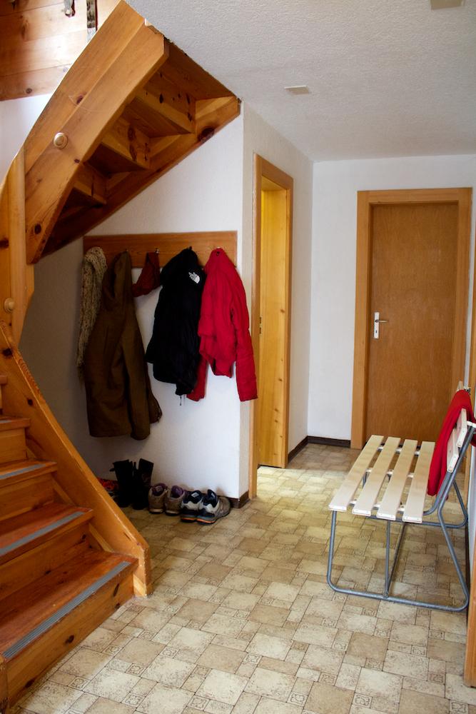 """De gang incl. """"natte-ruimte"""" voor ski's en schoenen (onder de trap)."""