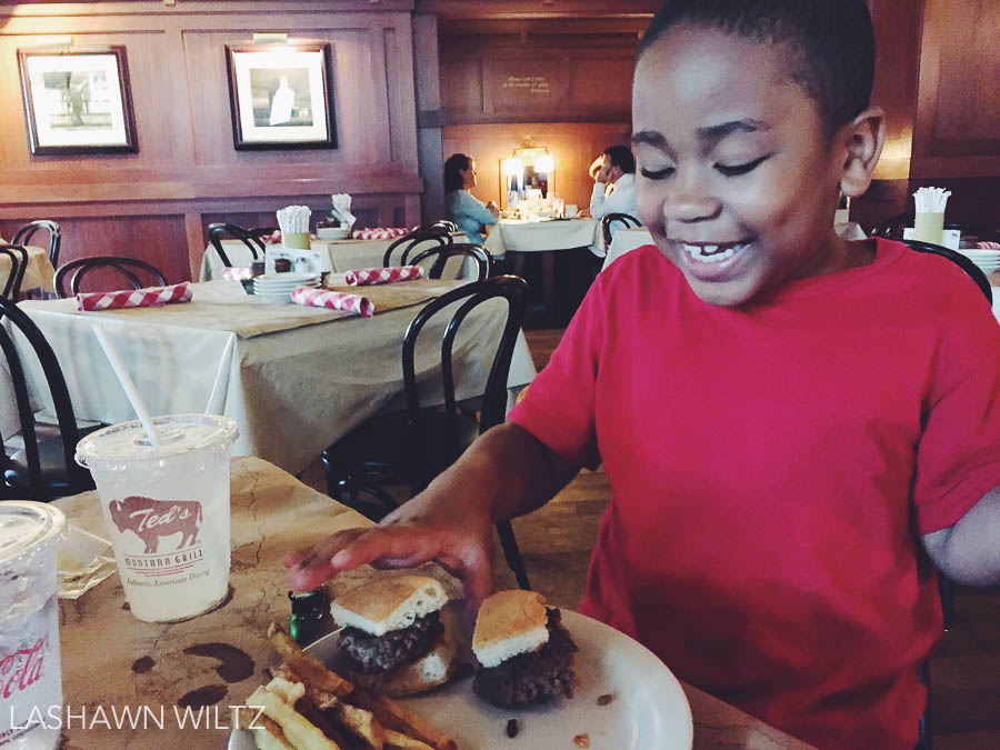 Boy gets his first hamburger on a bun