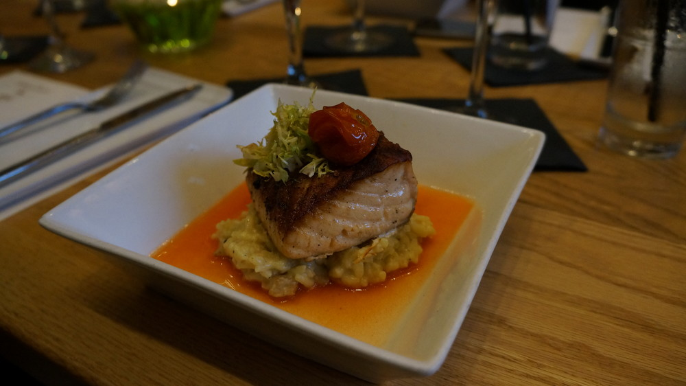 Pan Seared Salmon: The salmon is seasoned with salt and pepper, then pan seared. It is paired with a creamy ratatouille risotto, containing roasted eggplant, sautéed zucchini, and roasted tomatoes. The risotto rests in a sweet red pepper consumme (broth), and the salmon adorns the dish.