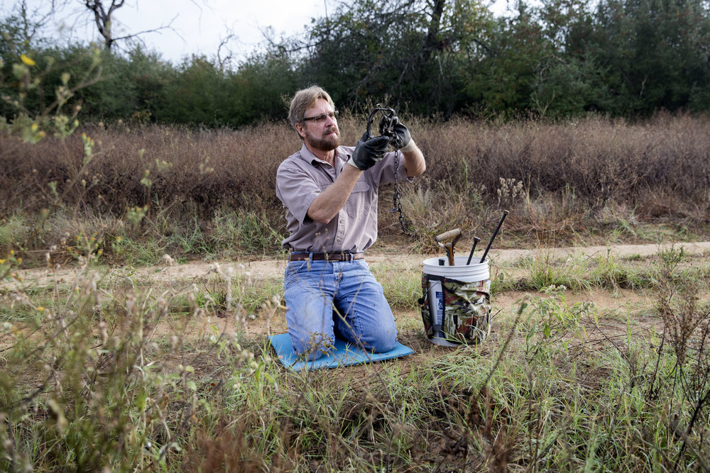 Trapper and outdoorsman Dan Hepker sets a coyote trap on a 900-acre ranch outside of Bastrop, Texas. (Shot and reported for Reporting Texas)