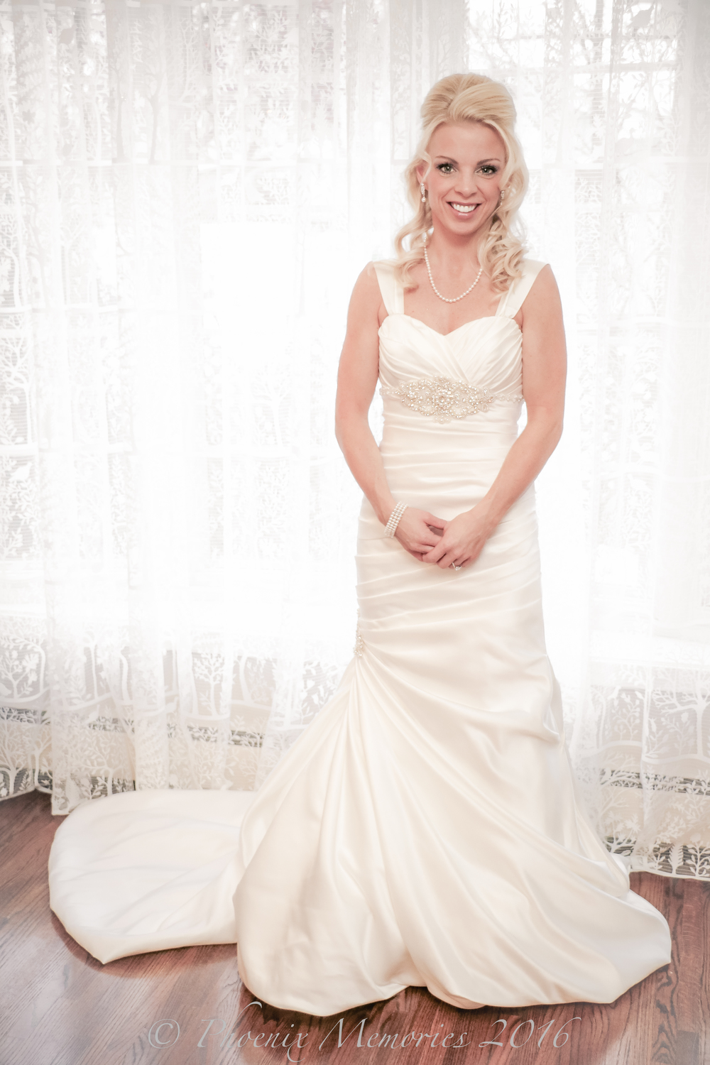 Sarah is ready to walk down the aisle with her completed bridal look from head to toe, with pearl necklace and earrings, jewel patterned bodice, pearl bracelet, and her gorgeous ring from  Shane Co. Jewelers.