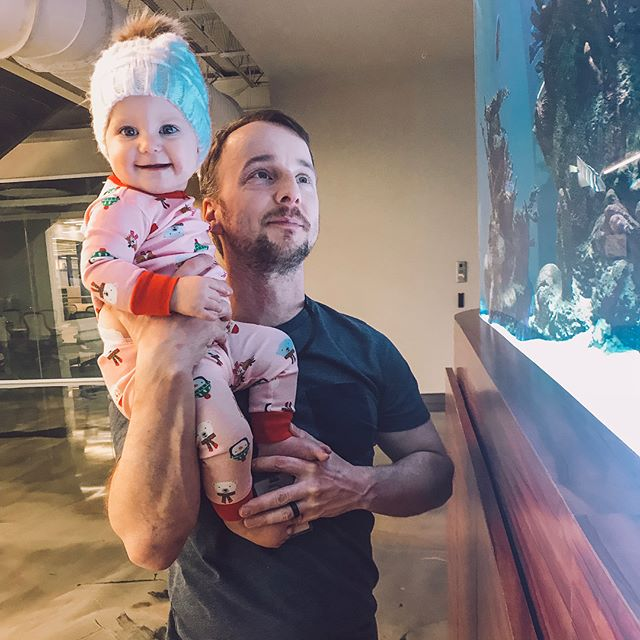 """Anna got to see the fish tank at Daddy's work for the first time on Friday. She was in awe and it was the cutest! 🐠 Swipe for a video of her saying """"oooooh!"""" 😍"""
