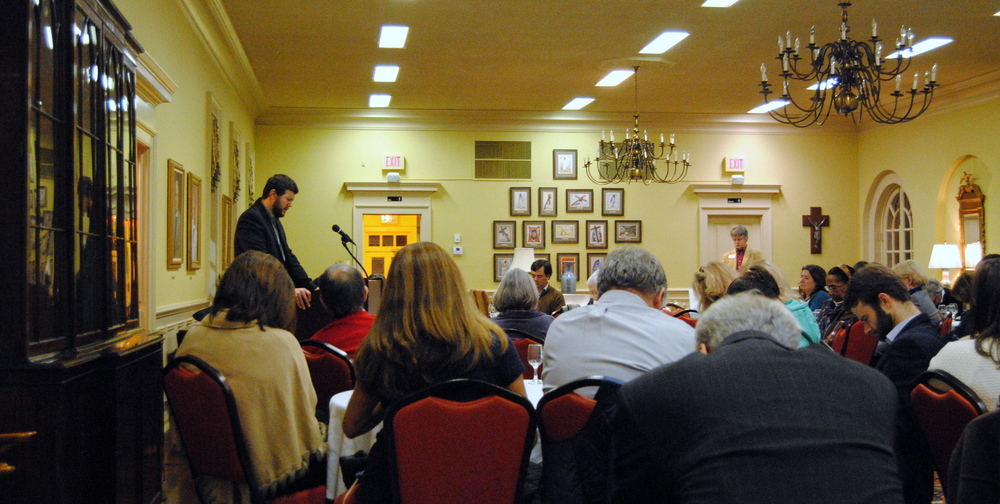 Michael Rhodes prays with the participants at a SOUL Supper
