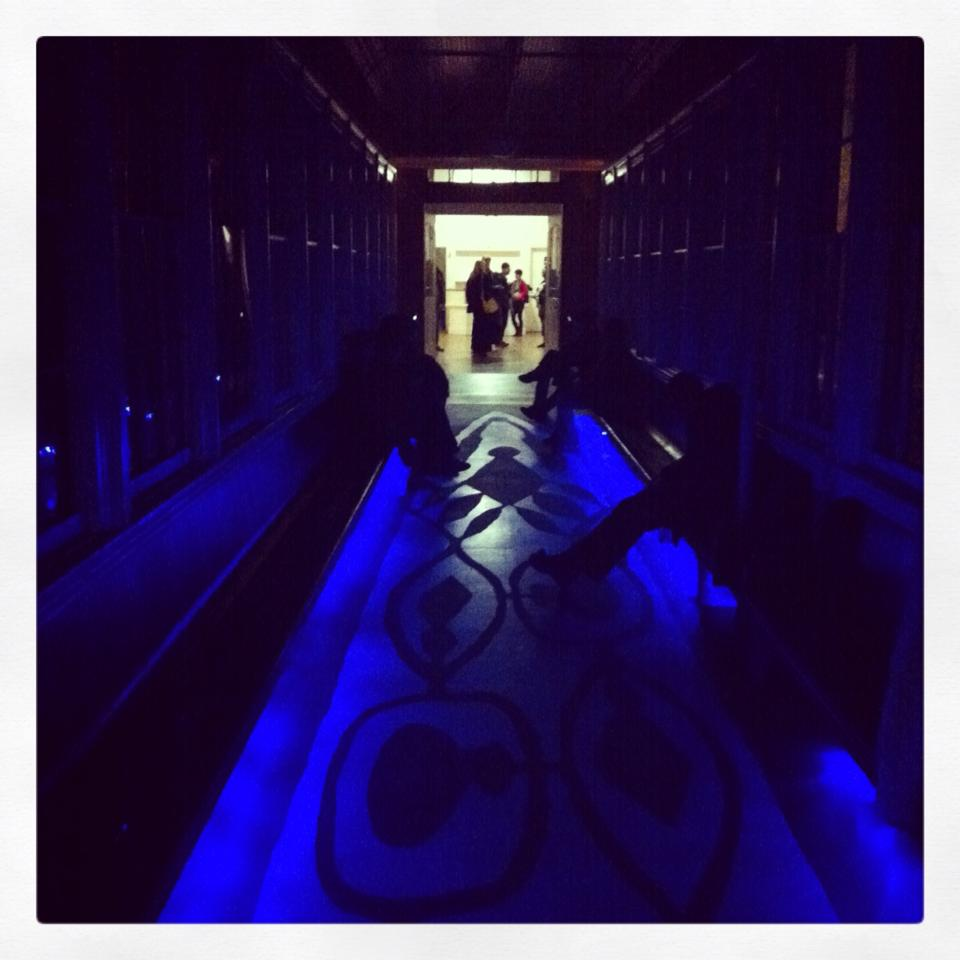 a passageway lined by benches and lit with blue light