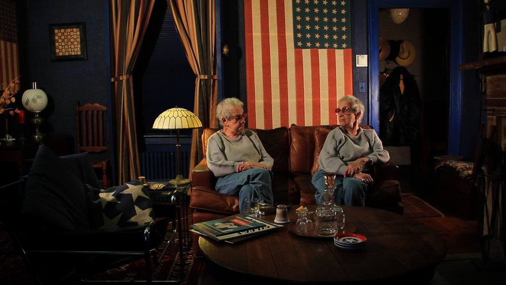 an older woman looks at a identical clone of herself. they sit on a sofa in a room decorated Americana