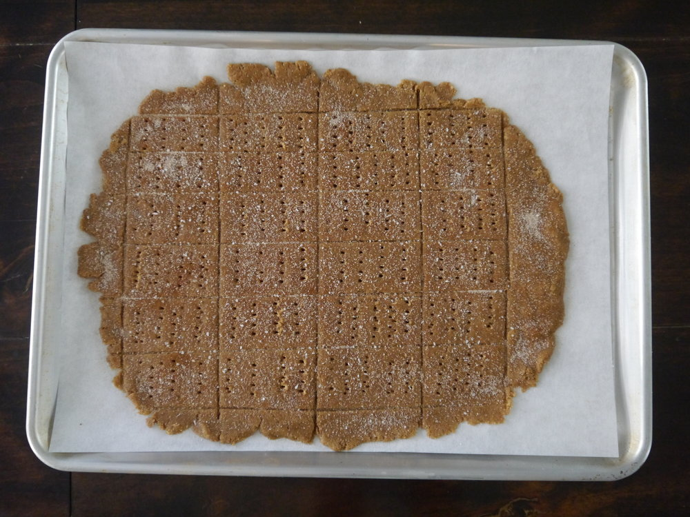 Using a bench scraper or knife, cut the rectangle into 1-by-2-inch rectangles, then poke the crackers with a fork to make dots. Slide the parchment (with the dough on it) onto the cookie sheet.