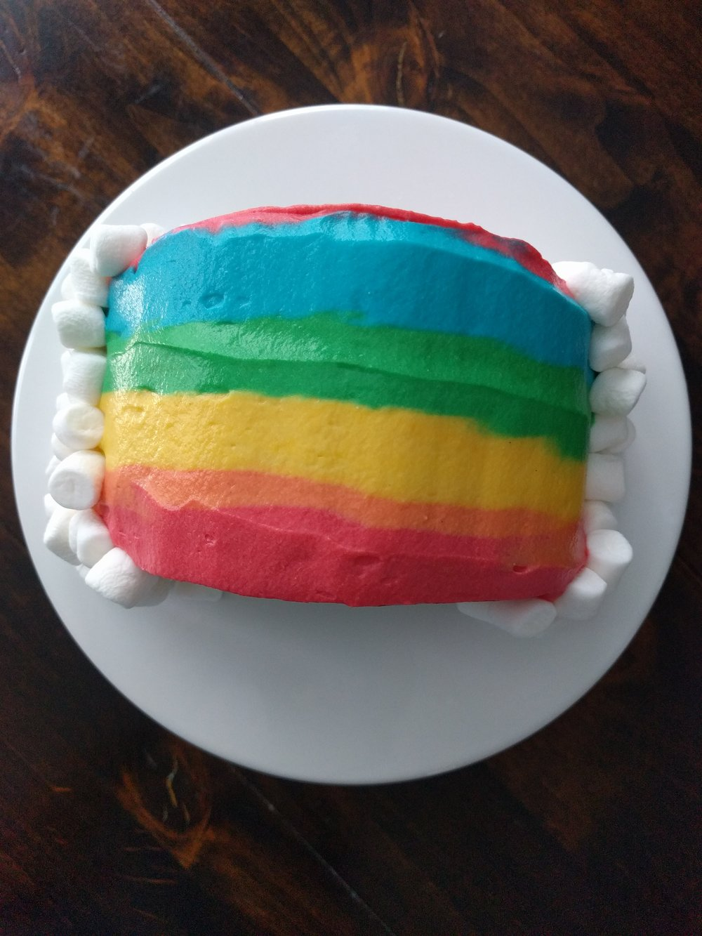 Do not try this at home. It is indescribably difficult to apply runny frosting in a rainbow of colors to a small cake.
