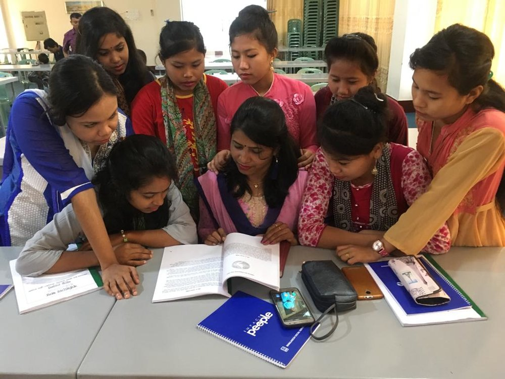"Young women in Bangladesh gather around our ""Esther Manual,"" as they dig deeper into lessons such as My Identity in Christ, Nurturing My Relationship With God, Servant Leadership, and Leading Where God Has Placed You."