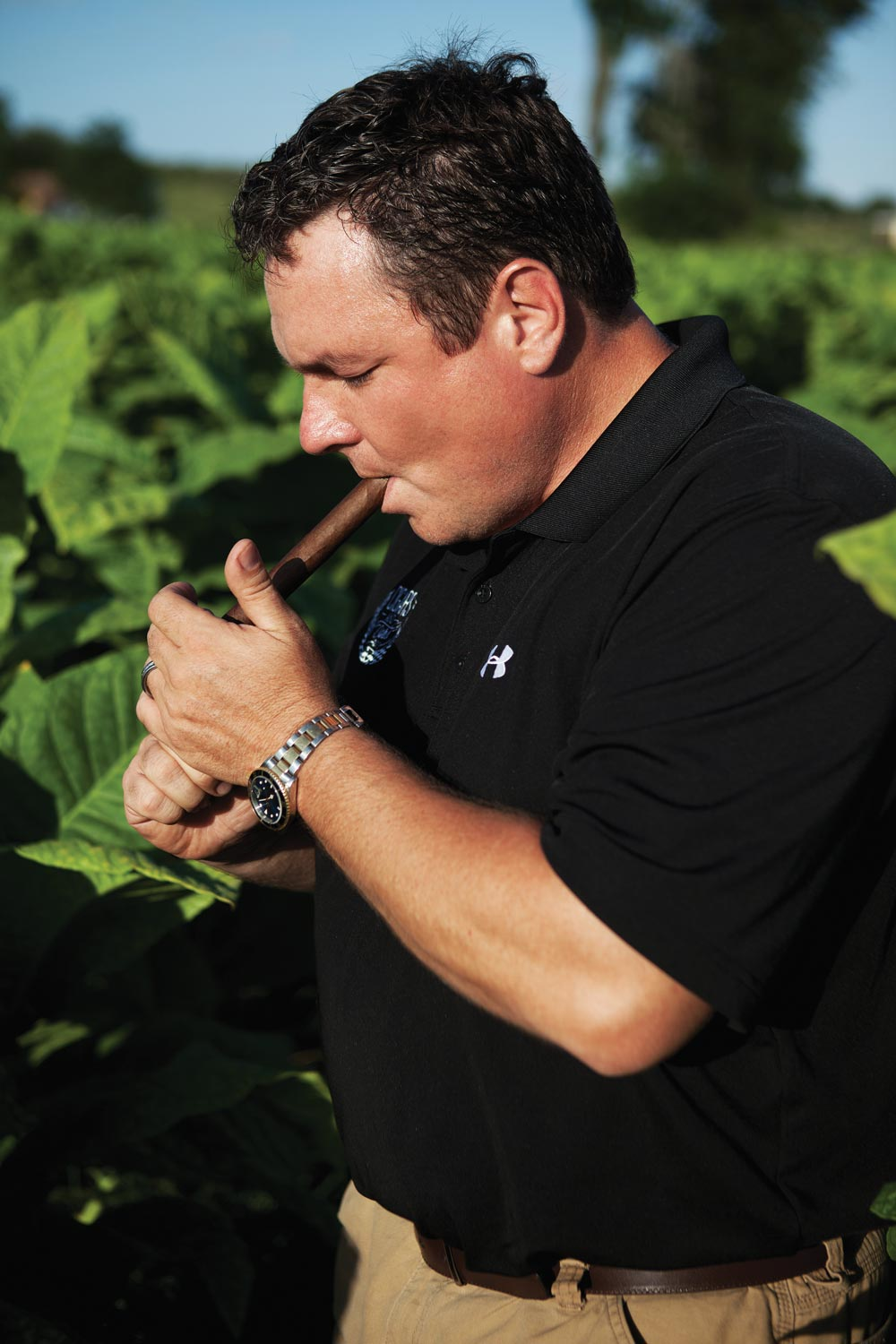 Jeff Borysiewicz smokes a cigar among the tobacco at his Florida Sun Grown tobacco farm in Central Florida. (image: Zach Ramsey)