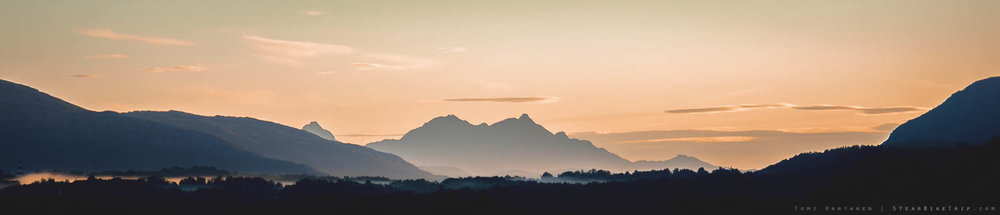 Misty view of distant mountain at sunset.