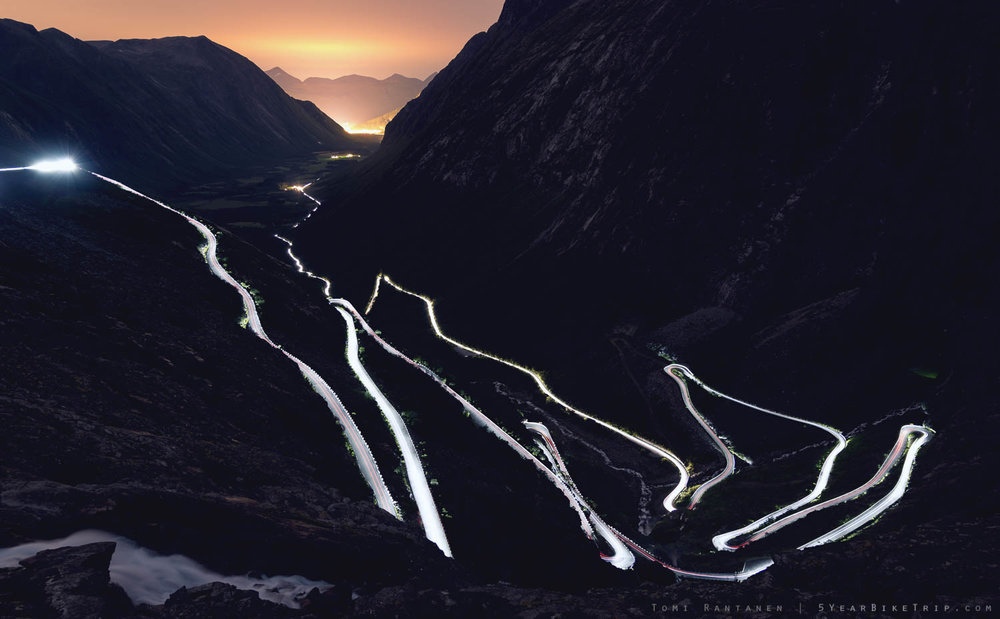 Car headlights painting Trollstigen at night.