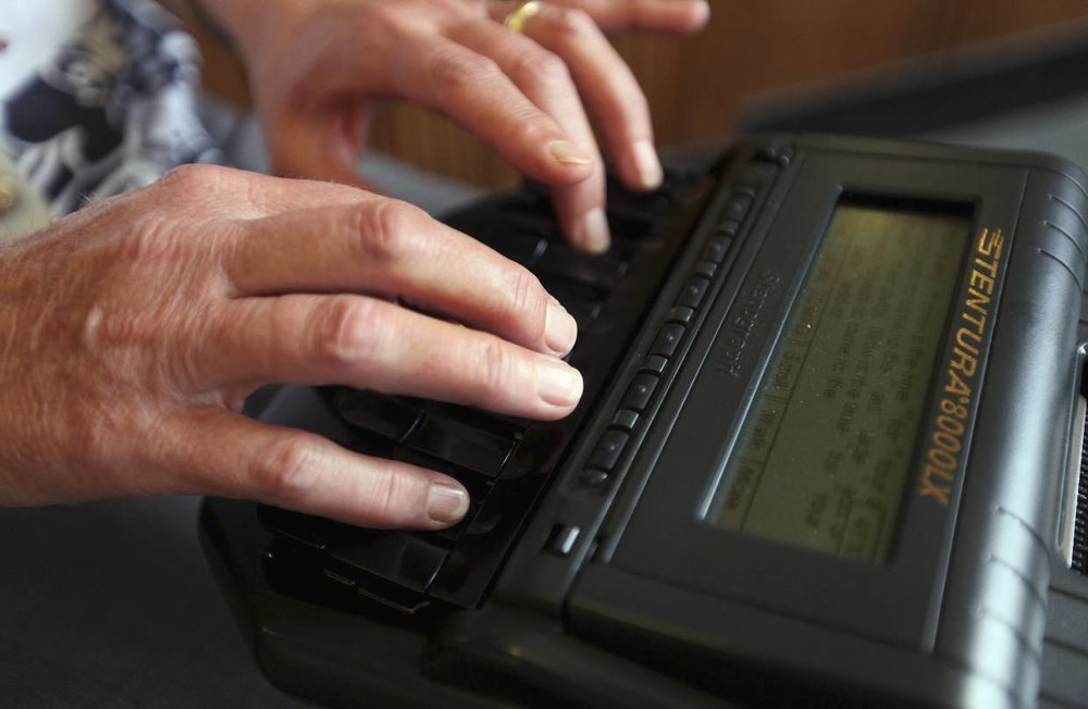 A court reporter types on a stenography machine in a Macon County circuit courtroom in Decatur, Ill., in July 2013. Court reporting, which includes work beyond the courts, is facing a shortage of workers. PHOTO: DANNY DAMIANI/HERALD & REVIEW/ASSOCIATED PRESS