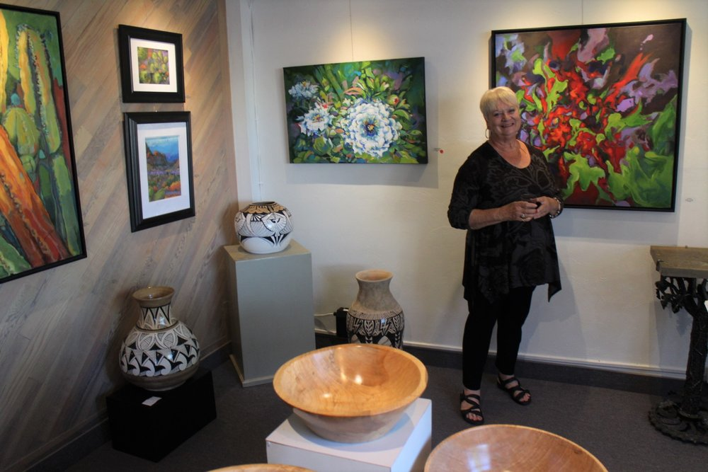 Jane Walter Bousman, standing among her paintings,was the featured June artist at Two Rivers Gallery