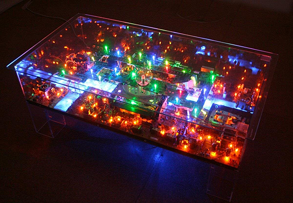 Benjamin Yates makes coffee tables that house miniature cities made from discarded gadgets and electronic parts. He also fills them with fairy lights and railroad figures of people to bring life to the cities. One man's trash is a little man's territory.