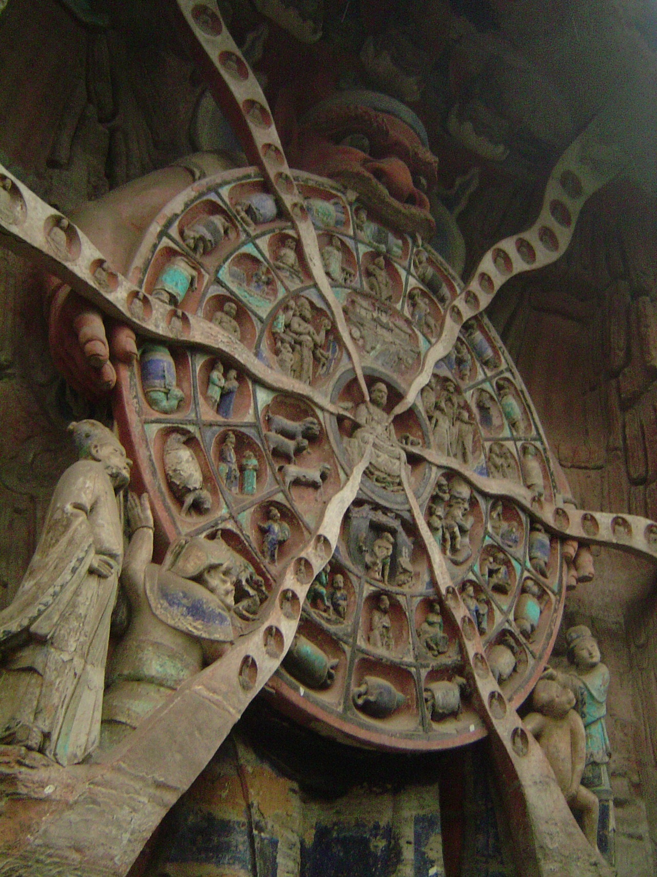 In this 8-meter tall Buddhist relief from the   Dazu Rock Carvings   in China, built sometime between the years 1177 and 1249,   Mara  , Lord of Death and Desire, clutches the Wheel of Reincarnation, which outlines the Buddhist cycle of reincarnation.