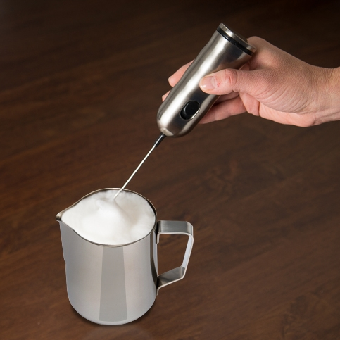 Milk frother froths foam in stainless steel frothing pitcher.jpg