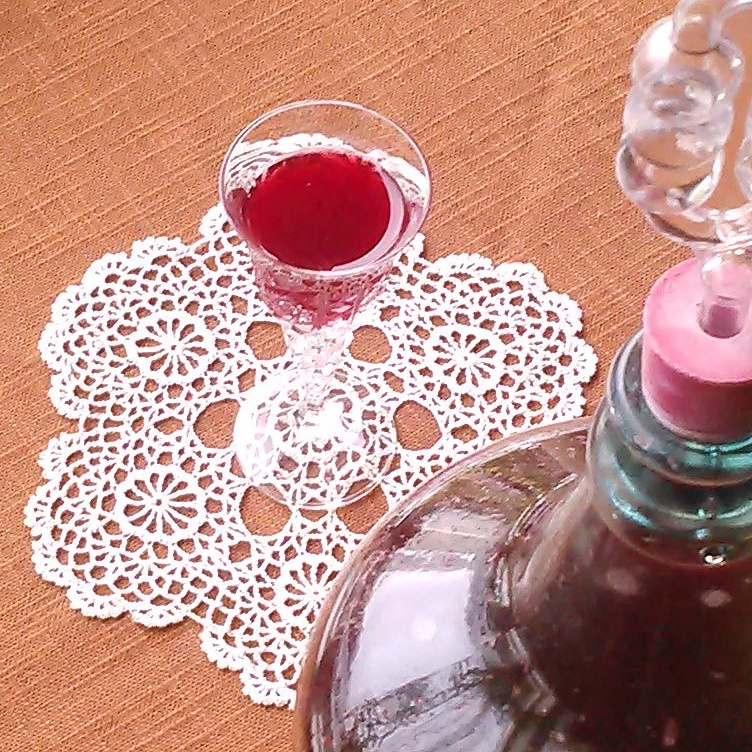 Feirer vintersolverv med et glass blåbærvin. Villgjæret vin.