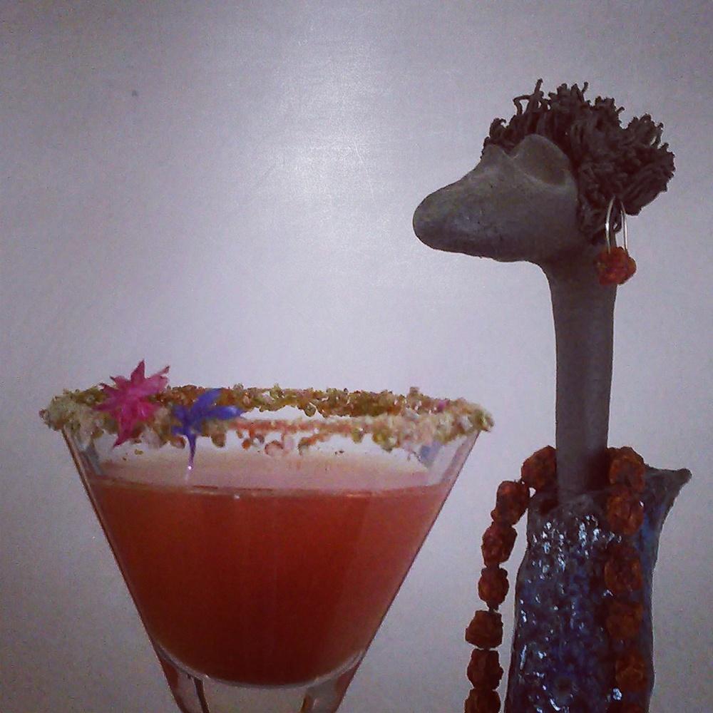 Rognebærsaft blandet med hvitvin. På kanten av glasset et blanding av granskuddsukker og tørket malt rognebær. Ørepynt og halskjede er også av tørkede rognebær :)