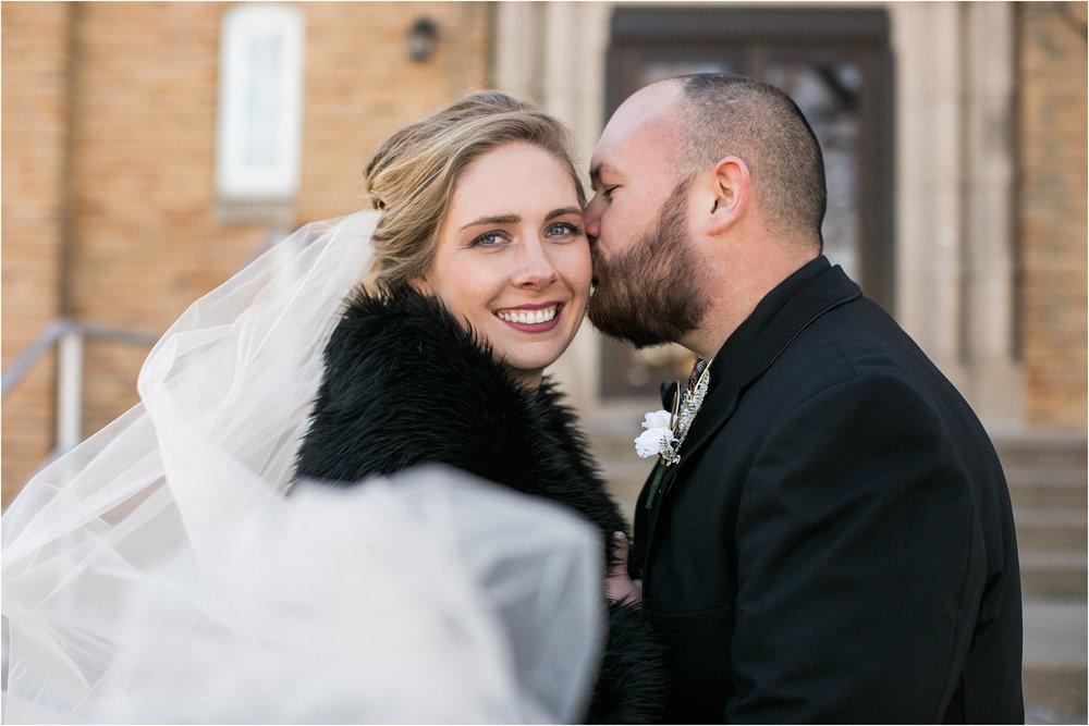 blowing veil groom kissing bride