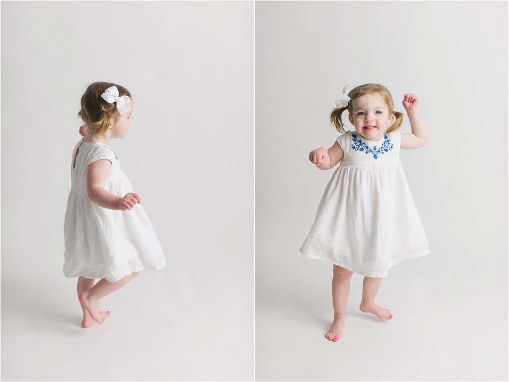 little girl dancing in a white dress on white background