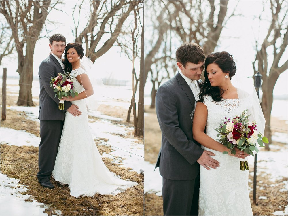 bride and groom posing in snowy grass with bold colored florals