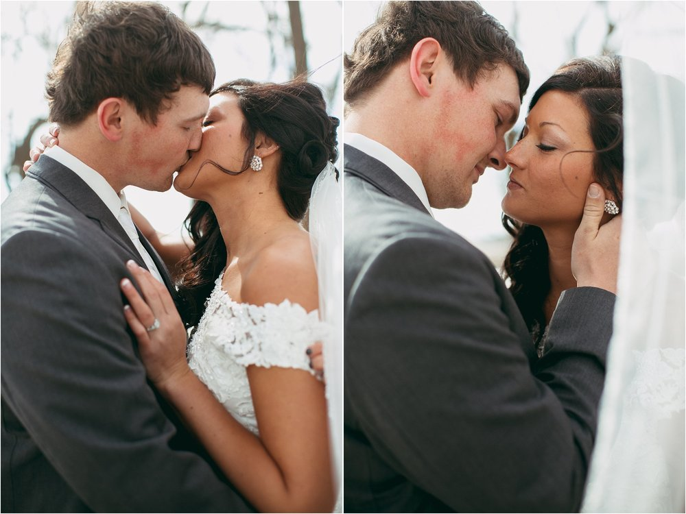 close up photo of bride and groom kissing through wedding veil