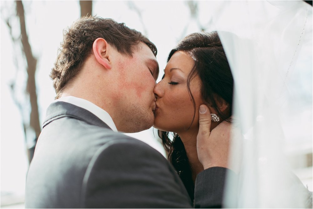 bride and groom kissing with veil blowing