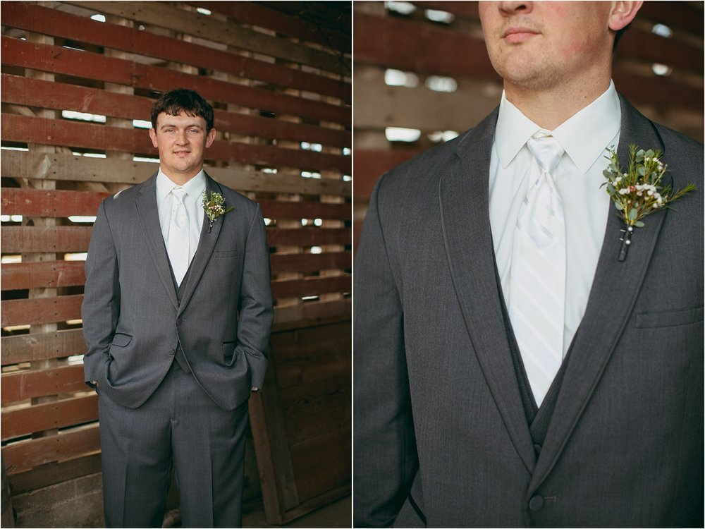 groom in a gray tux with white tie posing in an old corncrib