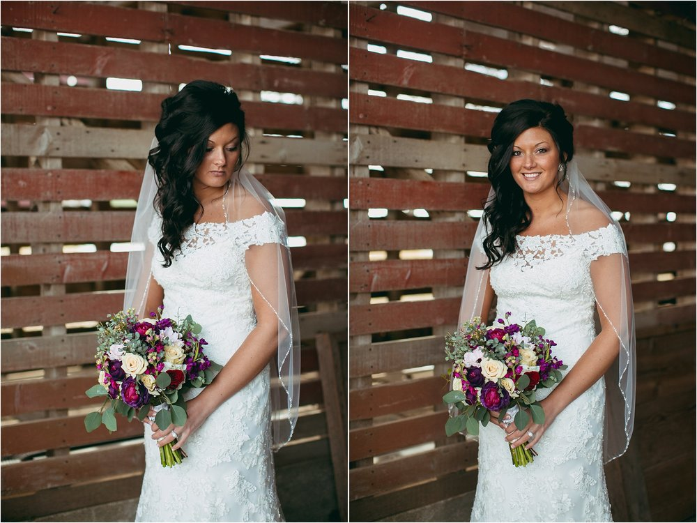 bride in old corncrib building with bold purple flowers