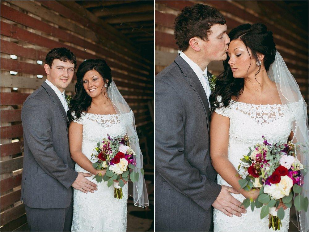 groom and bride posing in old corncrib building