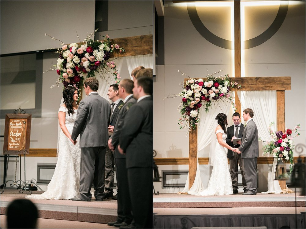 bride and groom holding hands at alter in front of barnwood arch