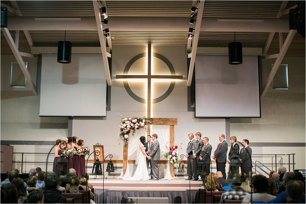 wedding ceremony with barnwood arch and large wooden cross