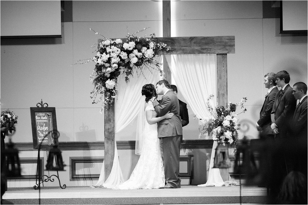 groom kissing his bride at the alter