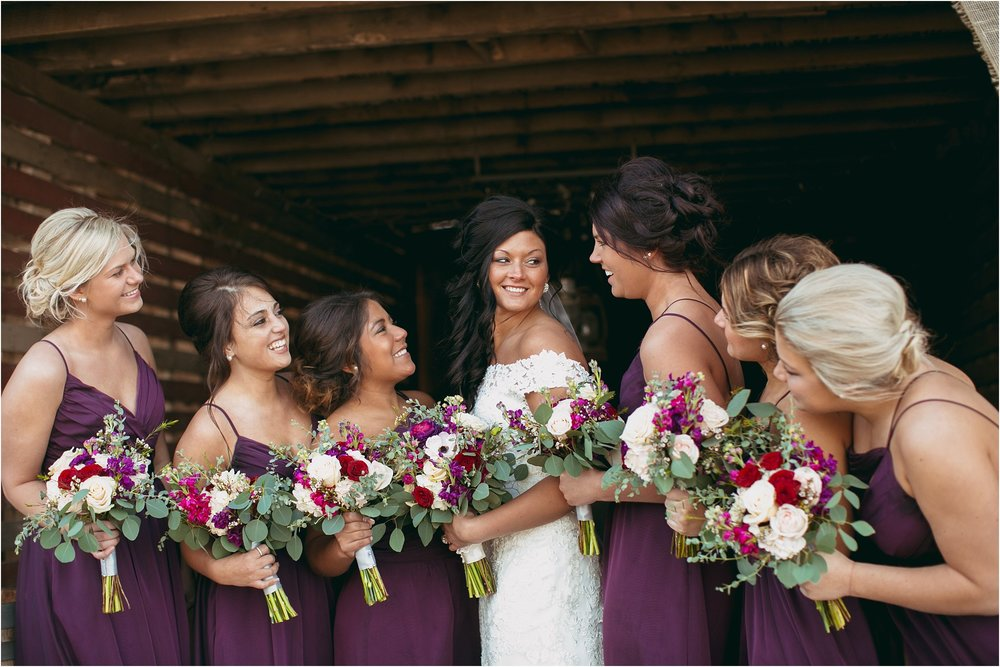 bridesmaids in purple dresses looking at bride