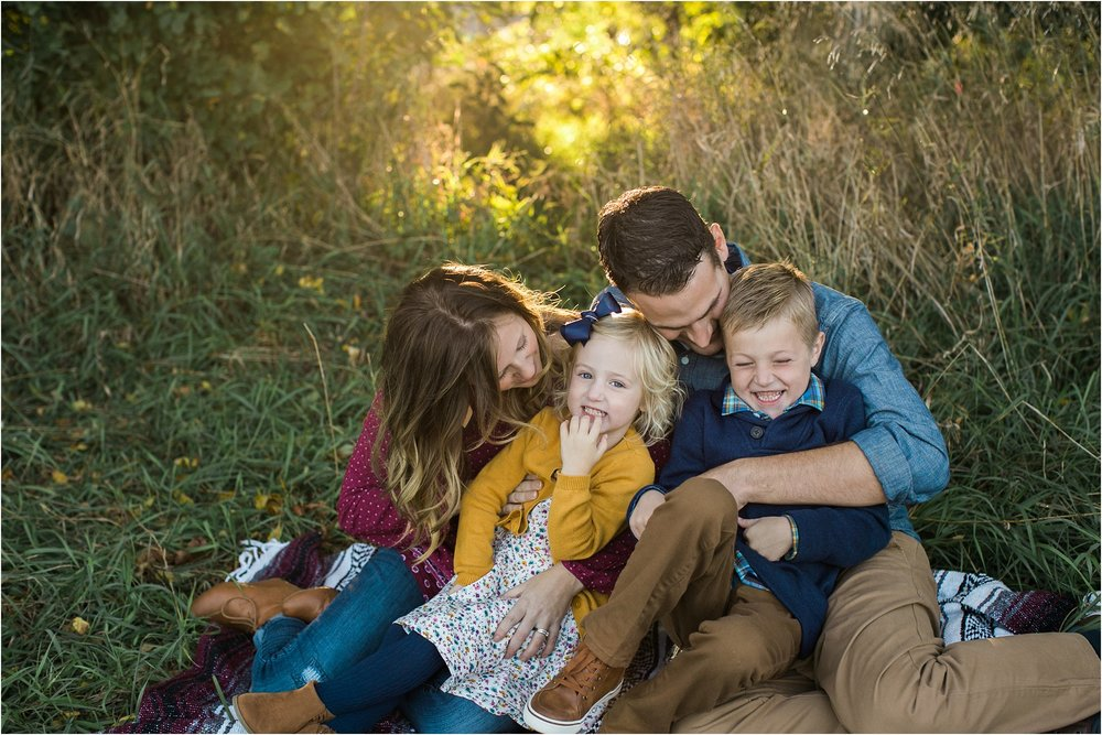family of four snuggling with kids laughing