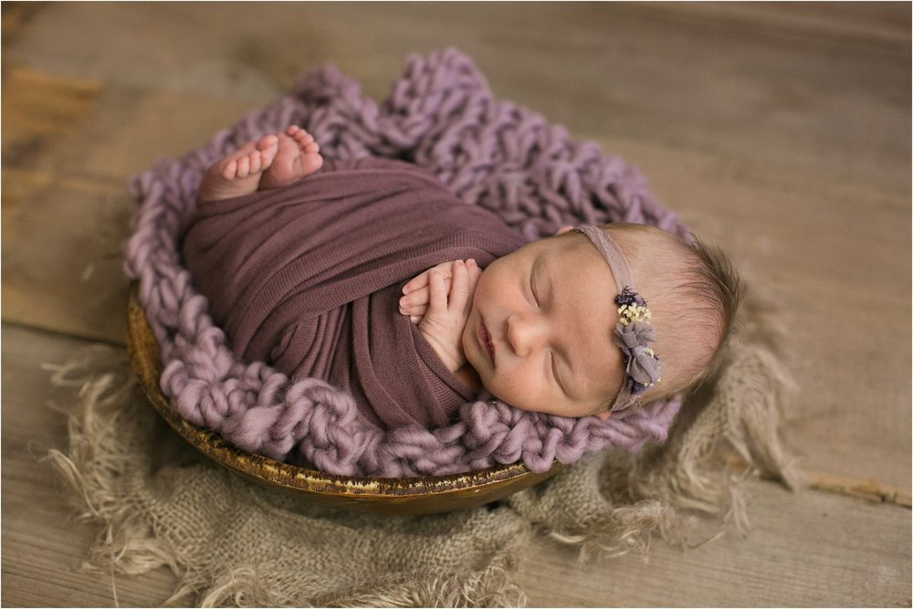 newborn girl wrapped in purple with burlap layer on barnwood