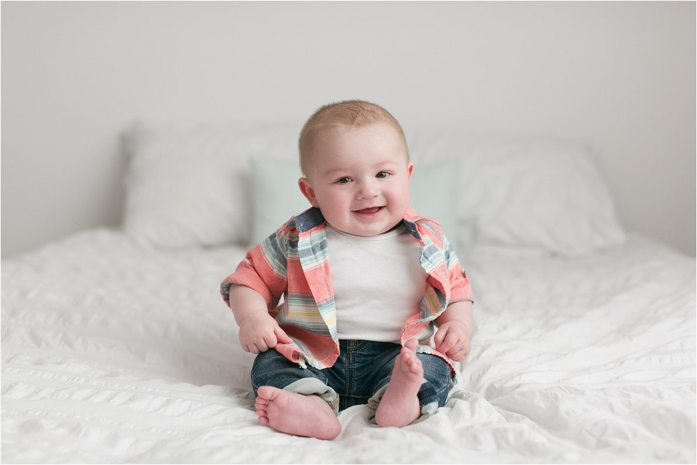 chubby baby boy sitting on white bed