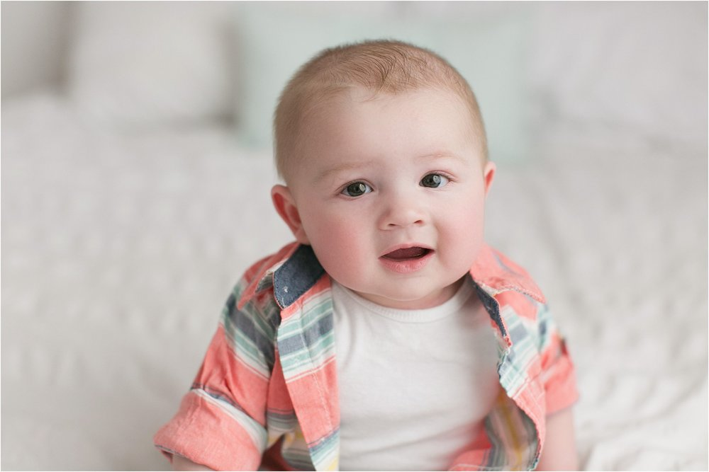 6 month old boy with colorful button up shirt on bed