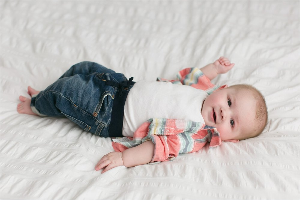 baby boy laying on white bed smiling