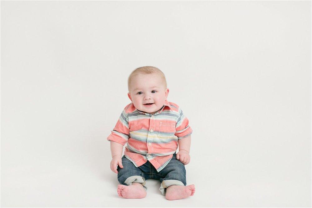 chubby baby boy sitting on white background