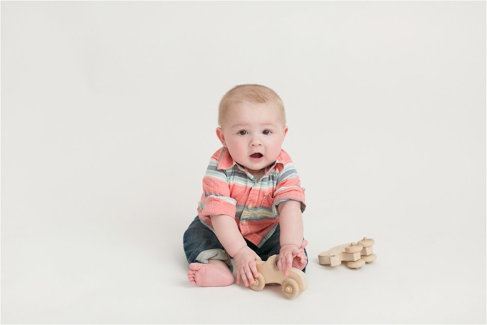 baby boy playing with wooden cars 6 months old