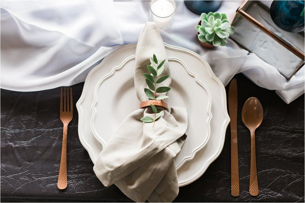 wedding plate setting with copper silverware and gray napkins