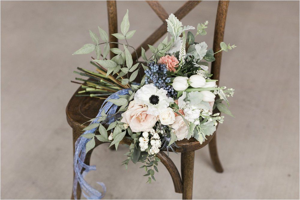 wedding bouquet with soft dusty blue tulips pale pink roses anemones and greenery