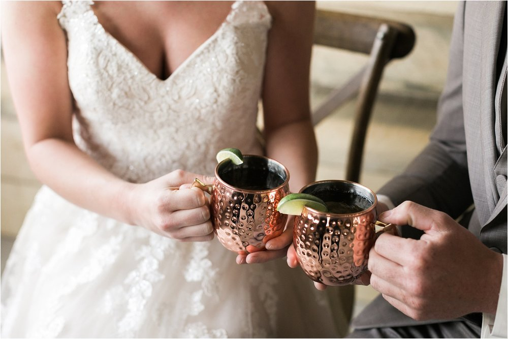 bride and groom clinking moscow mule copper mugs