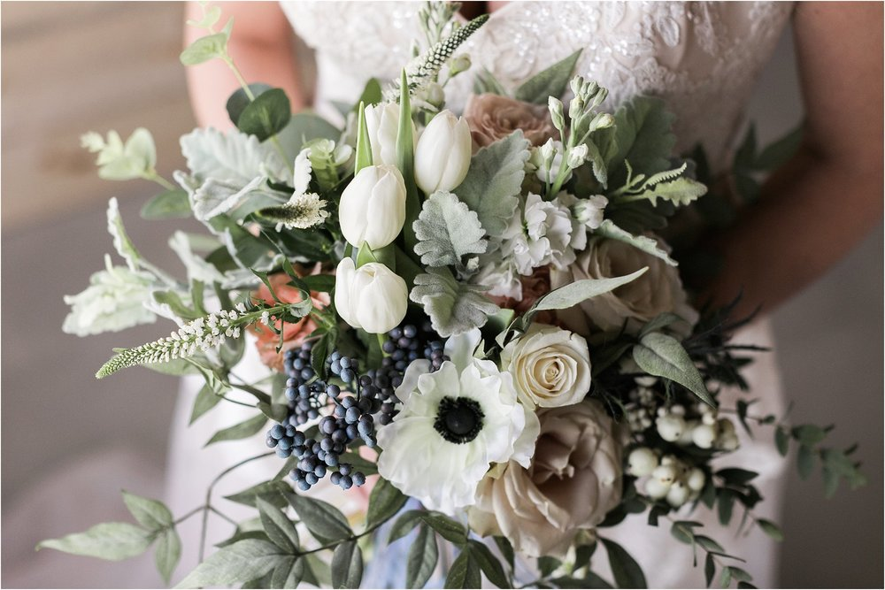 wedding bouquet full of soft colors tulips roses greenery dusty blue ribbon