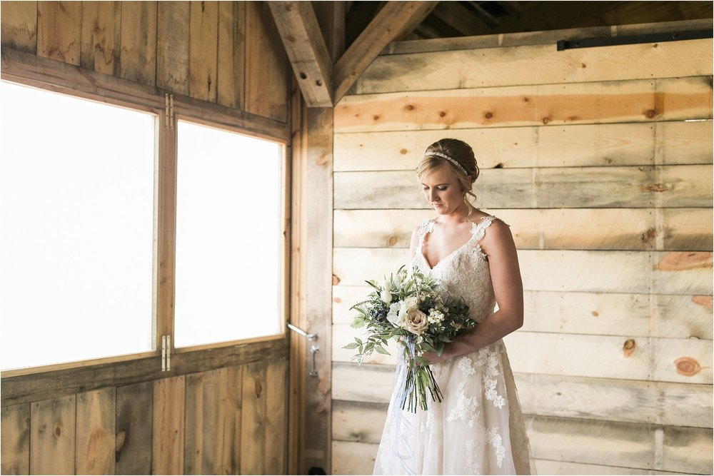 bride looking at her bouquet standing near windows in a barn