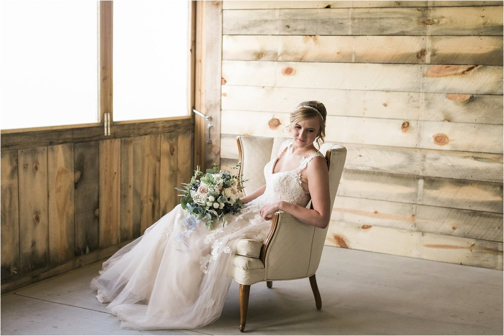 bride posing in a barn on a vintage chair