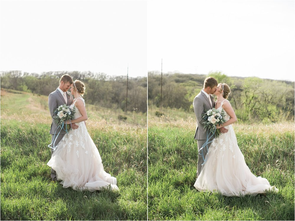 bride and groom kissing on a hilltop