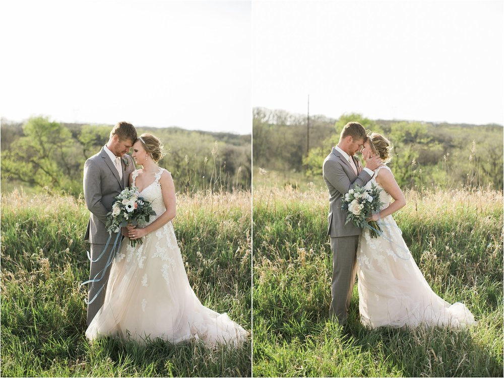 groom embracing his bride on a hilltop with tall grasses
