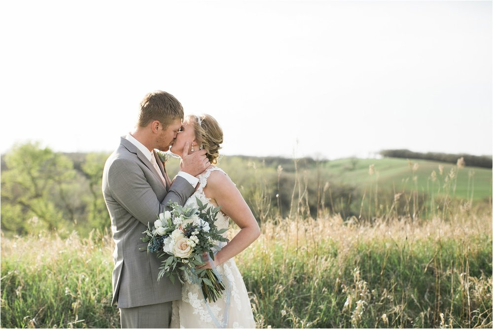 Bride and groom kissing on rolling hills